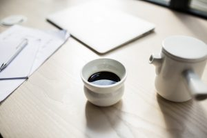 Cup of coffee with a small pot milk on a table in The Visit